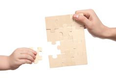 Mens and childs hands finishing set of puzzles Stock Image