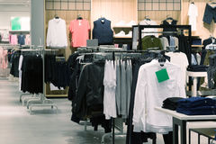 Mens clothes hanging on hangers in store Stock Image