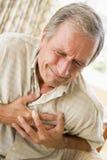 Mens Clutching Zijn Hart stock afbeelding