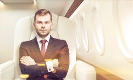 Mens in commerciële gestemde klasse van een vliegtuig, Royalty-vrije Stock Afbeelding