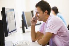 Mens in computerzaal die cellulaire telefoon met behulp van Stock Afbeelding