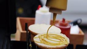 Mens Cook Hamburgers Pouring Mustard op Broodjes op de Hete Grill in de Zomer stock videobeelden