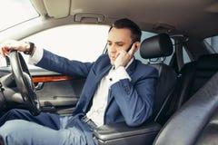 Mens in de auto lezing en het telefoneren Stock Foto