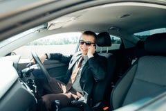 Mens in de auto lezing en het telefoneren Royalty-vrije Stock Foto