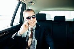 Mens in de auto lezing en het telefoneren Royalty-vrije Stock Fotografie