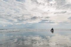 Mens in de berijdende motorfiets van GLB op strand Moto dwarsdirtbiker op strandzonsondergang op Bali Jong hipstermannetje die va stock foto's