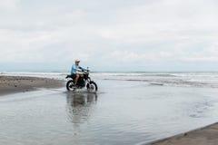 Mens in de berijdende motorfiets van GLB op strand Moto dwarsdirtbiker op strandzonsondergang op Bali Jong hipstermannetje die va royalty-vrije stock afbeeldingen
