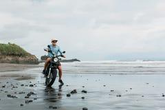 Mens in de berijdende motorfiets van GLB op strand Moto dwarsdirtbiker op strandzonsondergang op Bali Jong hipstermannetje die va stock afbeelding