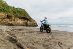 Mens in de berijdende motorfiets van GLB op strand Moto dwarsdirtbiker op strandzonsondergang op Bali Jong hipstermannetje die va royalty-vrije stock foto