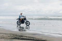 Mens in de berijdende motorfiets van GLB op strand Moto dwarsdirtbiker op strandzonsondergang op Bali Jong hipstermannetje die va stock fotografie