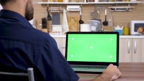 Mens in de keuken die computer met groene het scherm omhoog spot bekijken stock footage