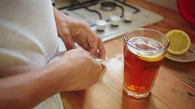 Mens in de keuken die thee met ijs voorbereiden stock video