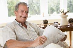 Mens in de krant van de woonkamerlezing het glimlachen Stock Afbeeldingen