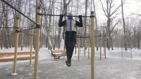 Mens de opleiding trekt oefening met fitness expander op openluchtsportgrond uit stock video