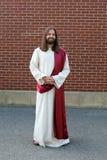 Mens in de robe van Jesus en sjerp naast bakstenen muur Stock Foto