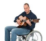 Mens in de rolstoel met gitaar Stock Foto