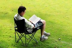 Mens in deckchairlezing royalty-vrije stock foto