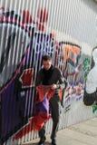 Mens dichtbij graffitymuur Stock Afbeeldingen