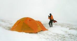 Mens dichtbij tent in sneeuwblizzard Royalty-vrije Stock Foto