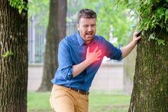 Mens die aan borstpijn lijden die hartaanval of pijnlijke cra hebben stock foto