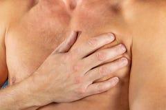 Mens die aan borstpijn lijden, die hartaanval of pijnlijke klemmen, die op borst met pijnlijke uitdrukking op blauwe backgound he stock afbeelding
