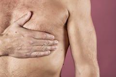 Mens die aan borstpijn lijden, die hartaanval of pijnlijke klemmen, die op borst met pijnlijke uitdrukking op roze backgound hebb royalty-vrije stock afbeelding