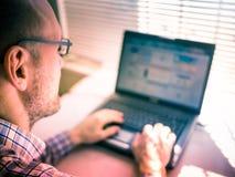 Mens die aan computer werken Stock Foto's