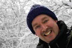 Mens die aan de Camera glimlacht terwijl Omringd door Sneeuw Gevulde Tak Stock Fotografie