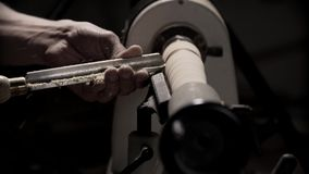 Mens die aan de machine van de houtbewerkingsdraaibank in timmermansworkshop werken met exemplaarruimte stock footage