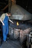 Mens die aan de smid van de steenkooloven werken Stock Foto's