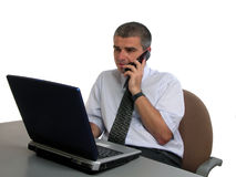 Mens die aan de telefoon bij het bureau spreekt Royalty-vrije Stock Foto