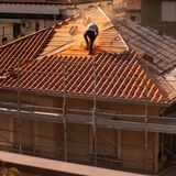 Mens die aan een dak en een steiger voor de vernieuwing van het oude gebouw werken royalty-vrije stock afbeelding