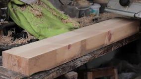 Mens die aan een houten schavende machine werken Spaandersvlieg in verschillende kant van planer stock footage