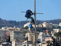 Mens die aan een mast van een schip werken stock afbeeldingen