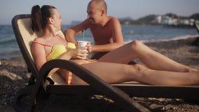 Mens die aan een meisje spreken die op een zonlanterfanter liggen met een cocktail stock video