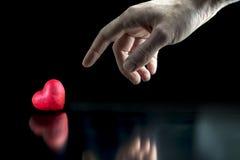 Mens die aan een rood hart richten Stock Foto