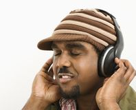 Mens die aan hoofdtelefoons luistert. stock foto