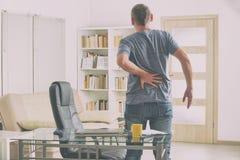 Mens die aan lage rugpijn lijden stock fotografie