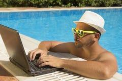 Mens die aan laptop bij de zwembadrand werken Stock Foto's