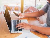 Mens die aan laptop computer met bedrijfsdocument werken en smartphone gebruiken stock afbeeldingen
