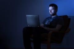 Mens die aan laptop in een donkere ruimte bij nacht werken stock afbeeldingen