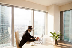 Mens die aan laptop met virtuele werkelijkheidsglazen werken Royalty-vrije Stock Foto's