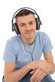 Mens die aan muziek in hoofdtelefoons op computer luistert Stock Afbeelding