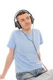 Mens die aan muziek in hoofdtelefoons van computer luistert Stock Afbeelding