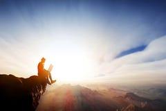 Mens die aan notitieboekje bovenop de bergen werken Internet-vrijheid Royalty-vrije Stock Afbeeldingen