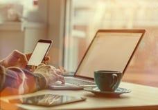 Mens die aan notitieboekje, met een verse kop van koffie en celtelefoon werken Royalty-vrije Stock Fotografie