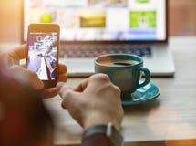 Mens die aan notitieboekje, met een verse kop van koffie en celtelefoon werken Stock Foto