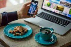 Mens die aan notitieboekje, met een verse kop van koffie en celtelefoon werken Royalty-vrije Stock Afbeeldingen