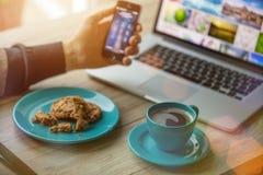 Mens die aan notitieboekje, met een verse kop van koffie werken Stock Foto