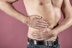 Mens die aan pijn in zijn kant lijden Roze achtergrond Maag, leverpijn, alvleesklier, nieren stock foto